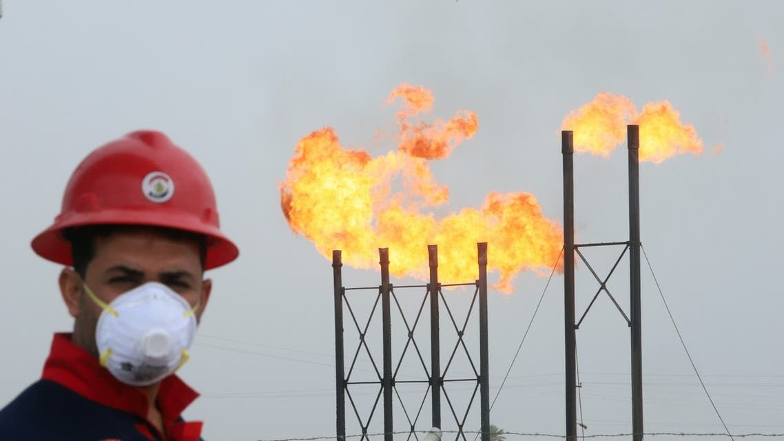 Flames emerge from flare stacks at Nahr Bin Umar oil field, as a worker wears a protective mask, following an outbreak of coronavirus, north of Basra, Iraq, March 15, 2020. (Reuters)