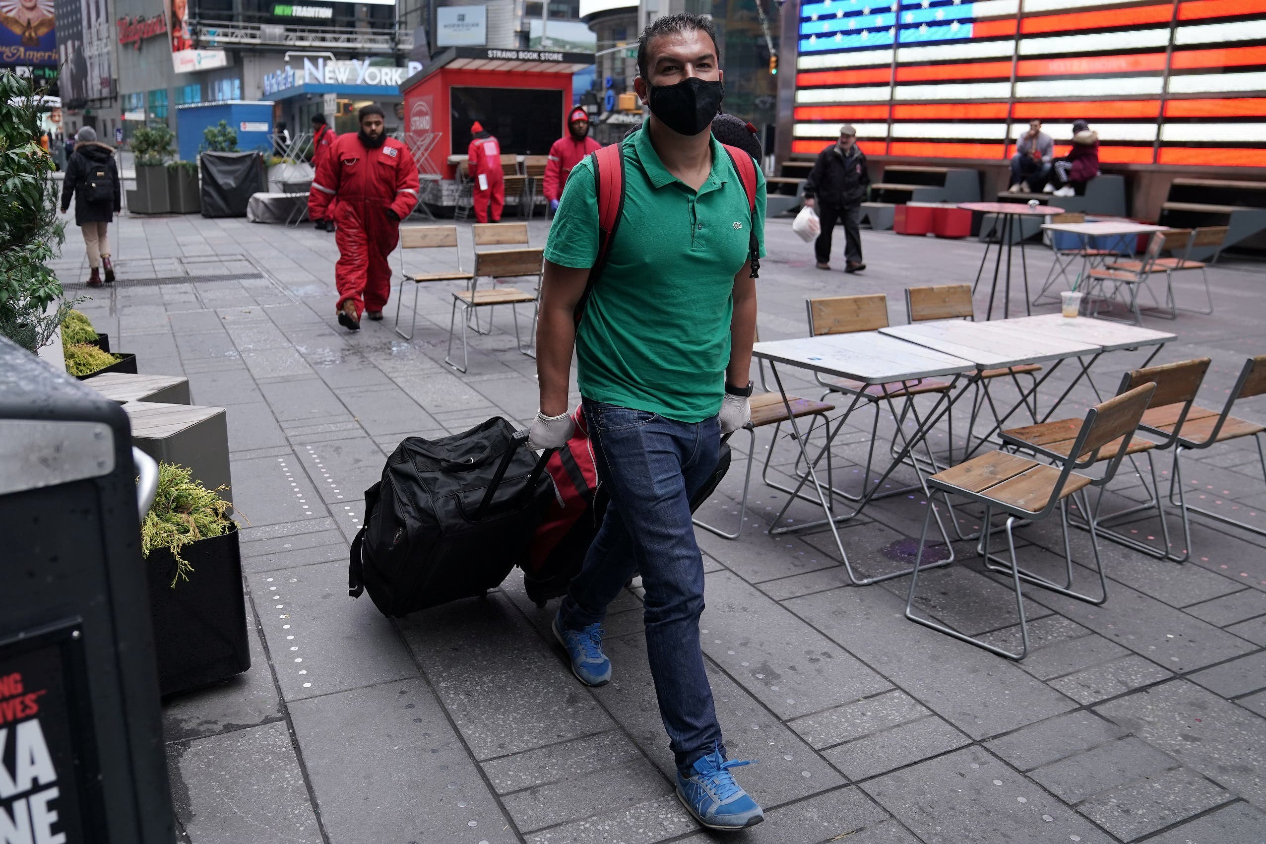 A man wearing a protective face mask walks with his luggage in Times Square, following the outbreak of Coronavirus disease (COVID-19), in the Manhattan borough of New York City, New York, US, March 19, 2020. (Reuters)