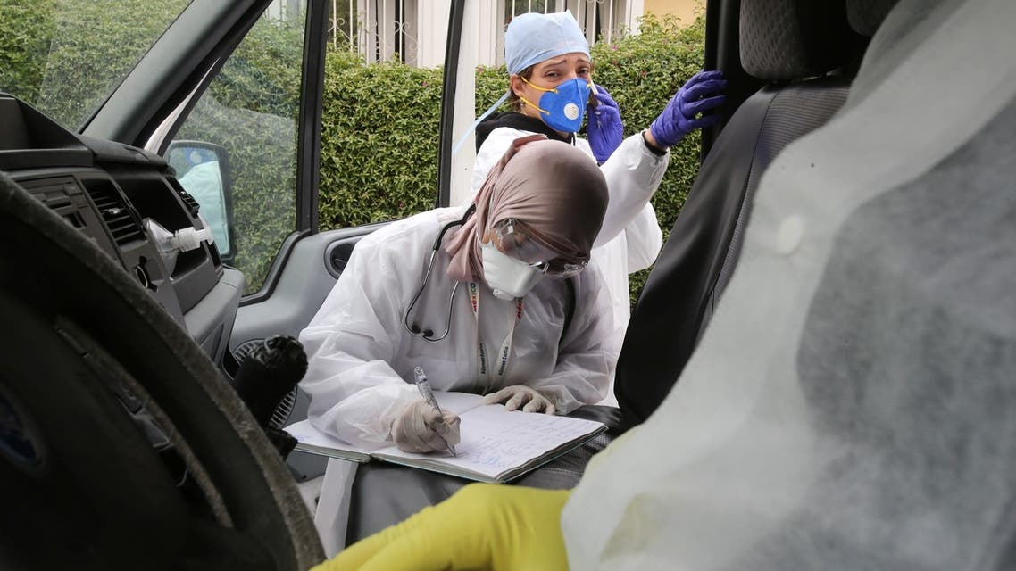 A member of the medical staff wearing a facial mask writes on file inside an ambulance at the hospital in Algiers, Algeria, on March 16, 2020. (Reuters)