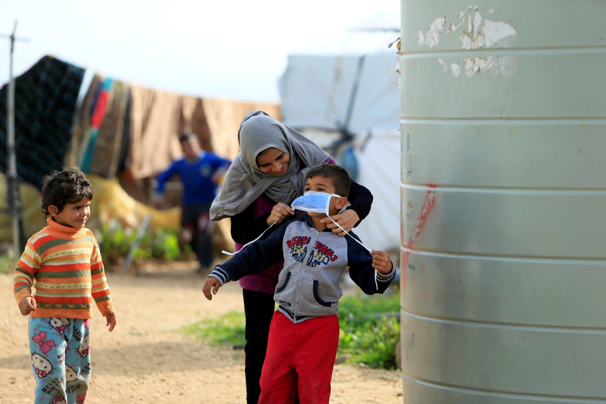 A Syrian refugee woman puts a face mask on a boy as a precaution against the spread of coronavirus, in al-Wazzani area, in southern Lebanon, March 14, 2020. (Reuters)