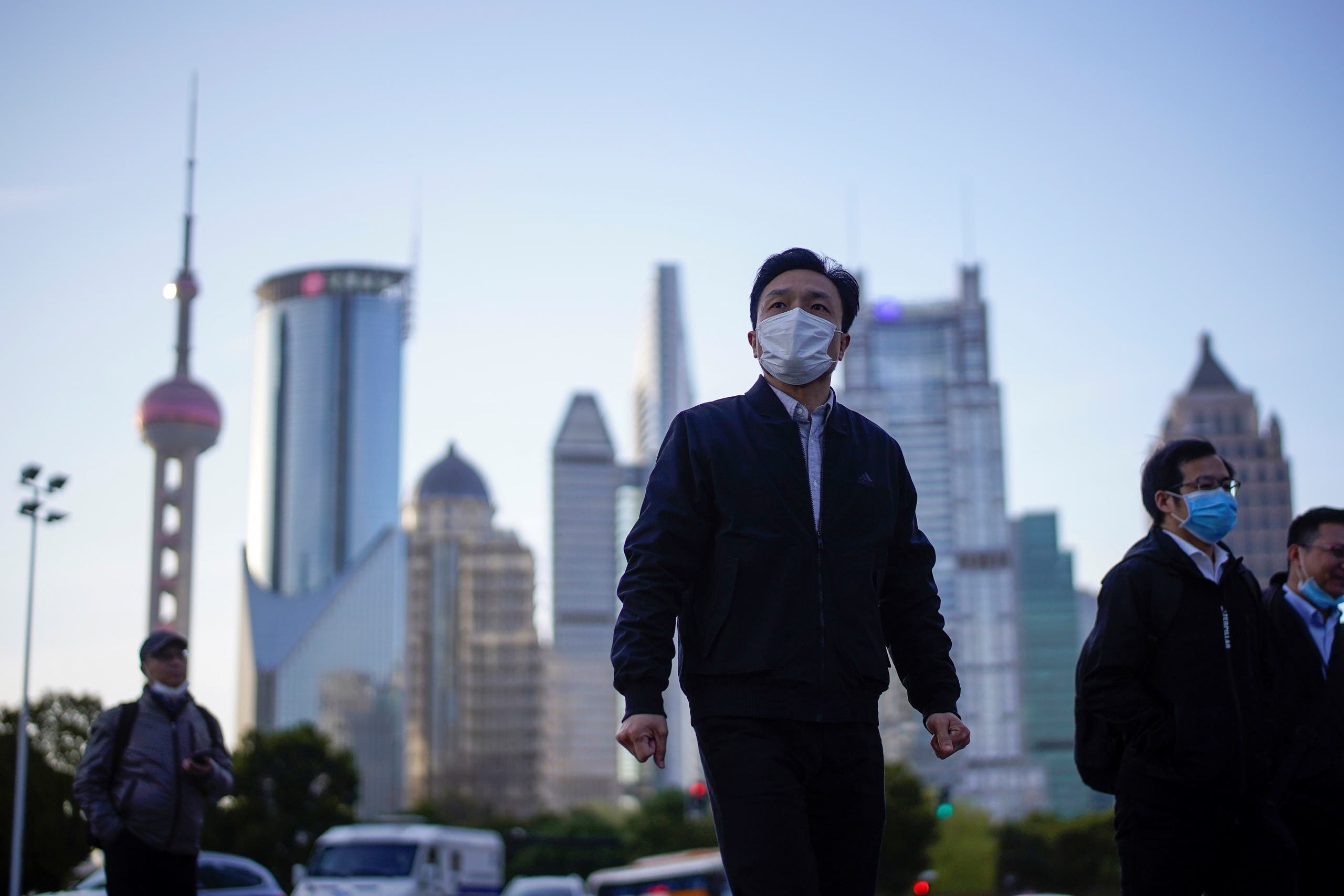 People wear protective face masks, following an outbreak of the novel coronavirus, at Lujiazui financial district in Shanghai, China, March 19, 2020. (File photo: Reuters)