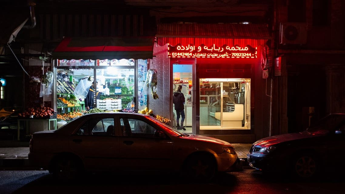 In the normally bustling Mar Mikhael neighborhood of Beirut, a fruit seller keeps his doors open while a butcher prepares to shut down his shop. (Finbar Anderson)