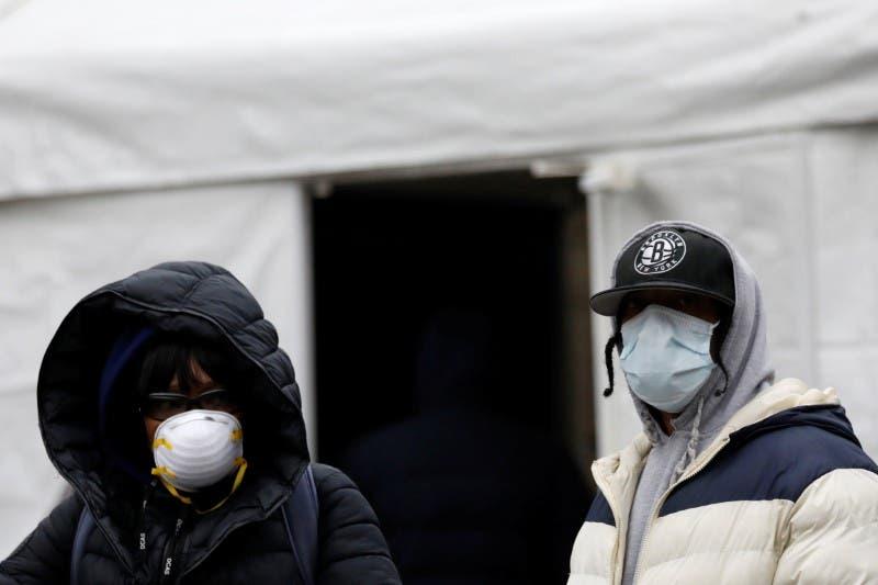 شخصان يرتديان كمامتان للوقاية من كورونا ويقفان بجانب خيمة للاختبار من الفيروس بمستشفى في بروكلين بنيويورك الخميس