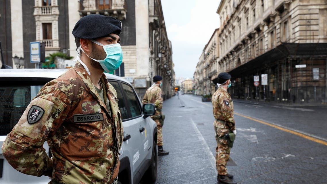Italian soldiers wearing protective masks work at a roadblock after Italy reinforced the lockdown measures to combat the coronavirus disease in Catania, Italy, March 21, 2020. (Reuters)