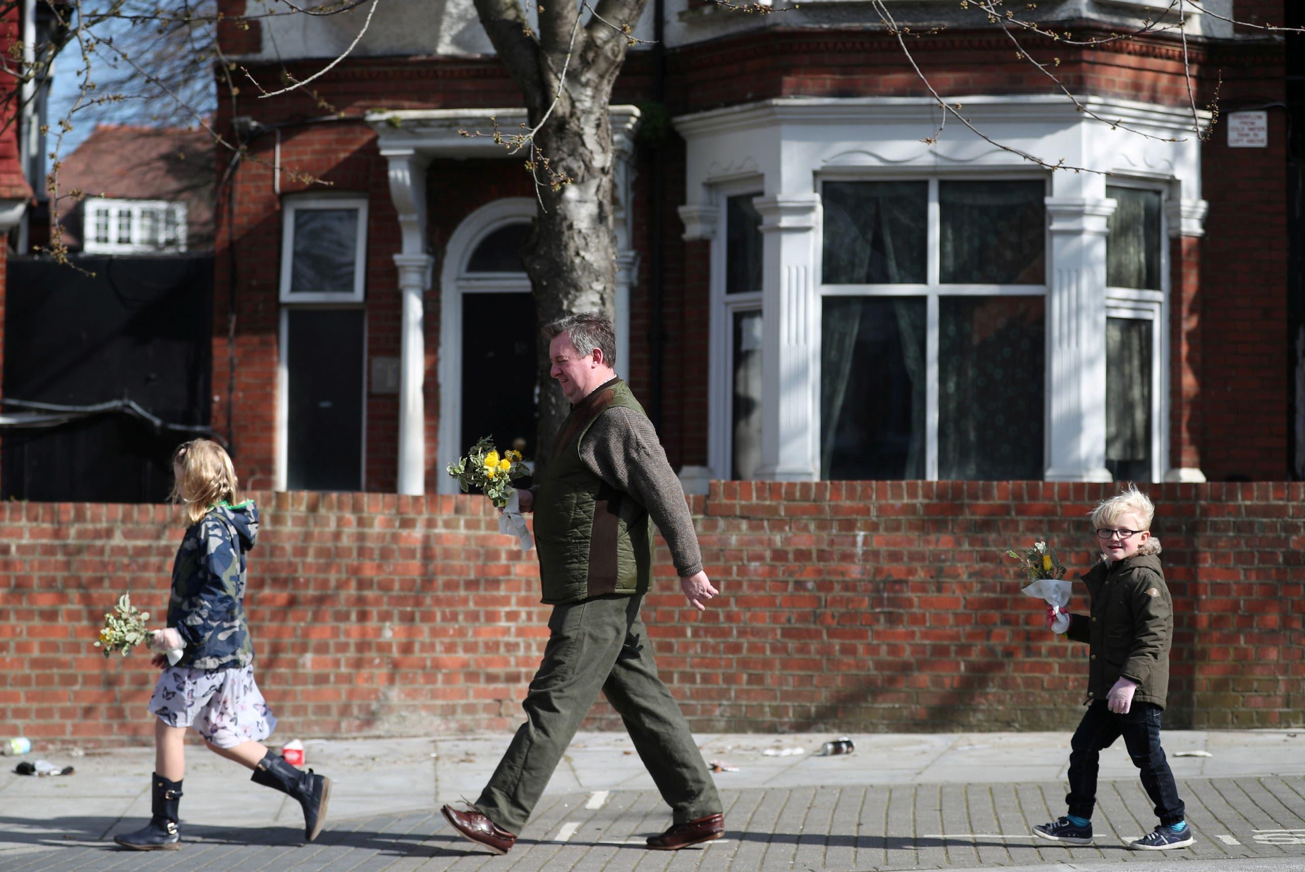رجل وطفلاه يحملون باقات زهور في إحدى ضواحي لندن بمناسبة عيد الأم