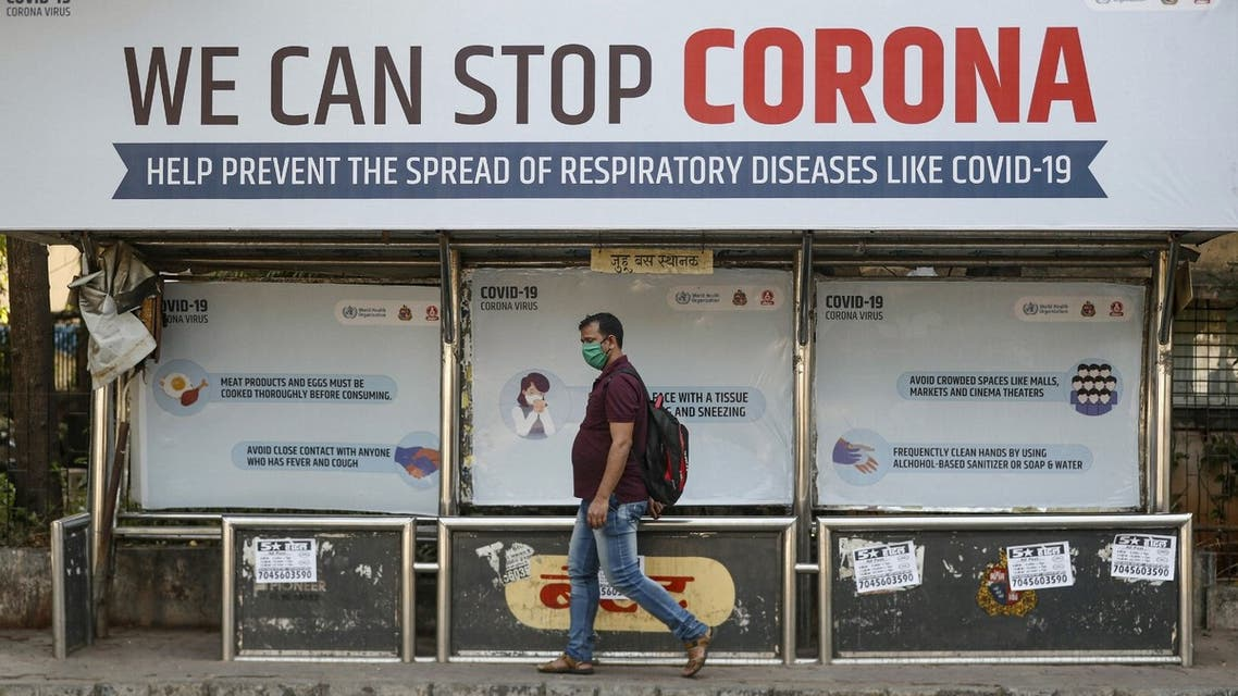 A man wearing a protective mask walks past a bus stop displaying preventive measures against the coronavirus in Mumbai, India, March 18, 2020. (Reuters)