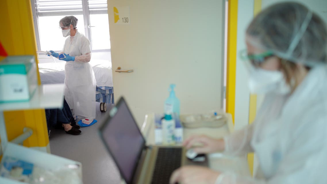 Medical workers wearing protective masks and suits are seen at the pulmonology unit at the hospital in Vannes where patients suffering from coronavirus disease (COVID-19) are treated, France, March 20, 2020. REUTERS/Stephane Mahe