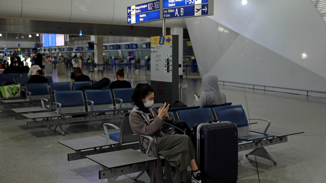 A passenger wearing a protective face mask checks her phone at the Athens International airport, following an outbreak of the coronavirus disease (COVID-19), in Athens, Greece, March 21, 2020. REUTERS/Alkis Konstantinidis