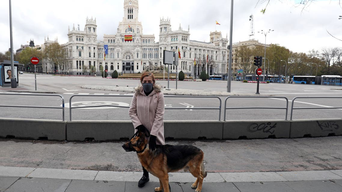 Maria del Carmen, 65, poses with her dog named Pulgas next to the Cibeles Fountain and City Hall building in Madrid. (Reuters)