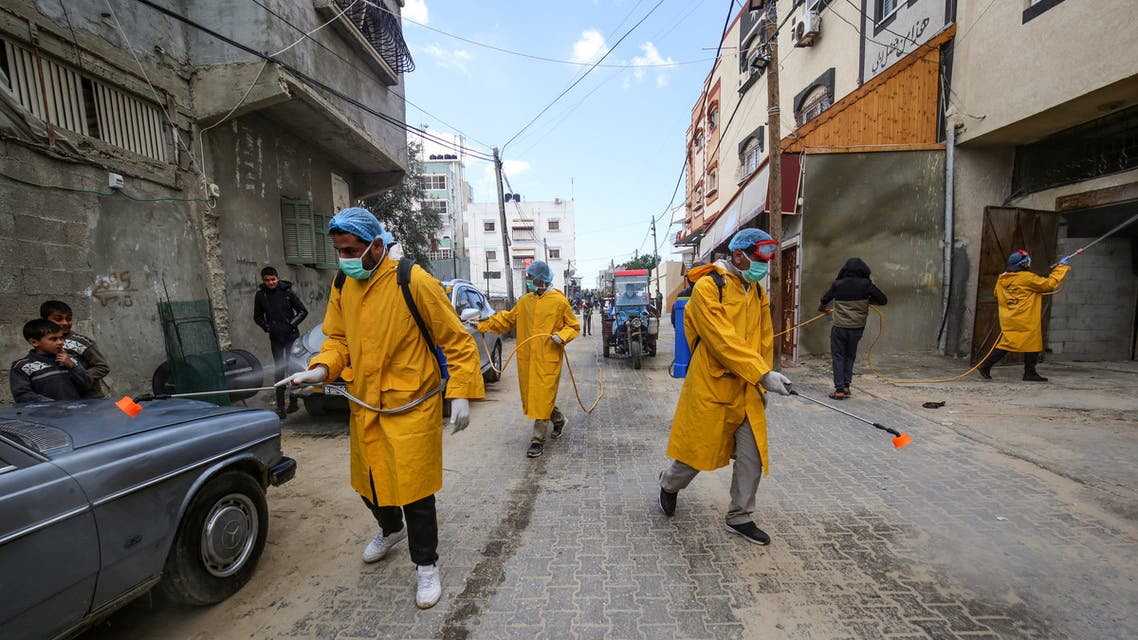 Palestinian volunteers wearing protective clothes and masks disinfect a street as a preventive measure against the spread of the novel coronavirus, in Rafah in the southern Gaza Strip, on March 22, 2020. Authorities in Gaza today confirmed the first two cases of novel coronavirus, identifying them as Palestinians who had travelled to Pakistan and were being held in quarantine since their return.