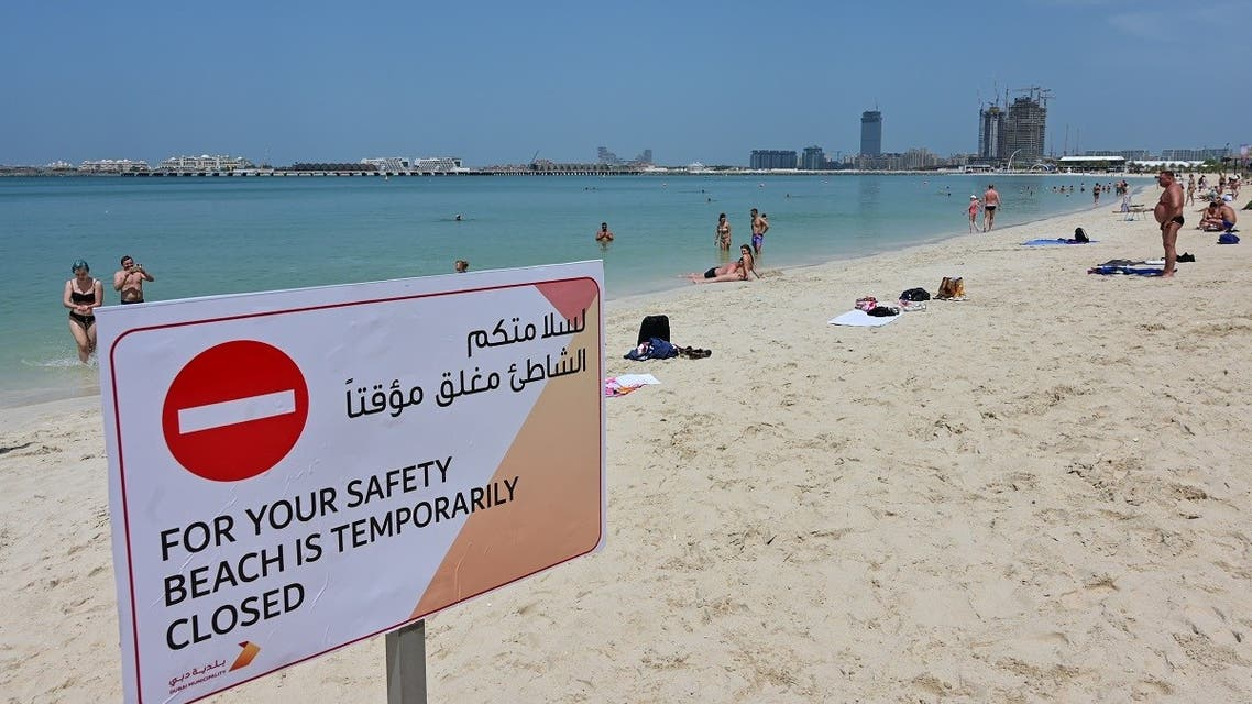 People take a sunbath along the Jumeirah Beach residence in Dubai on March 22, 2020 following its closure by authorities amid the COVID-19 coronavirus pandemic. (Reuters)