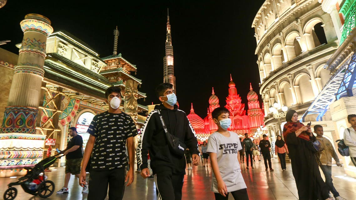 People wear protective masks, following an outbreak of coronavirus, as they walk at Global Village in Dubai. (Reuters)