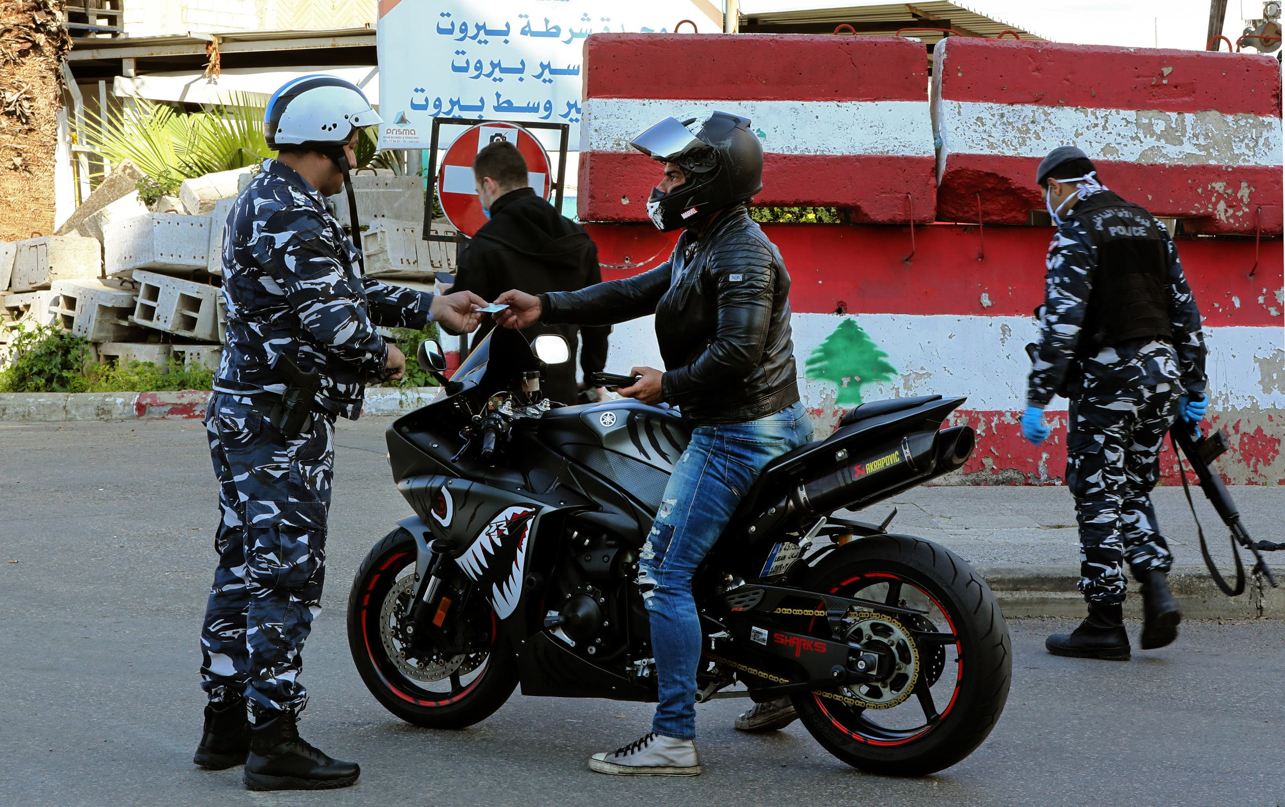 Lebanese security forces stop a man on a bike for violating coronavirus measures in central Beirut, March 22. (Reuters)