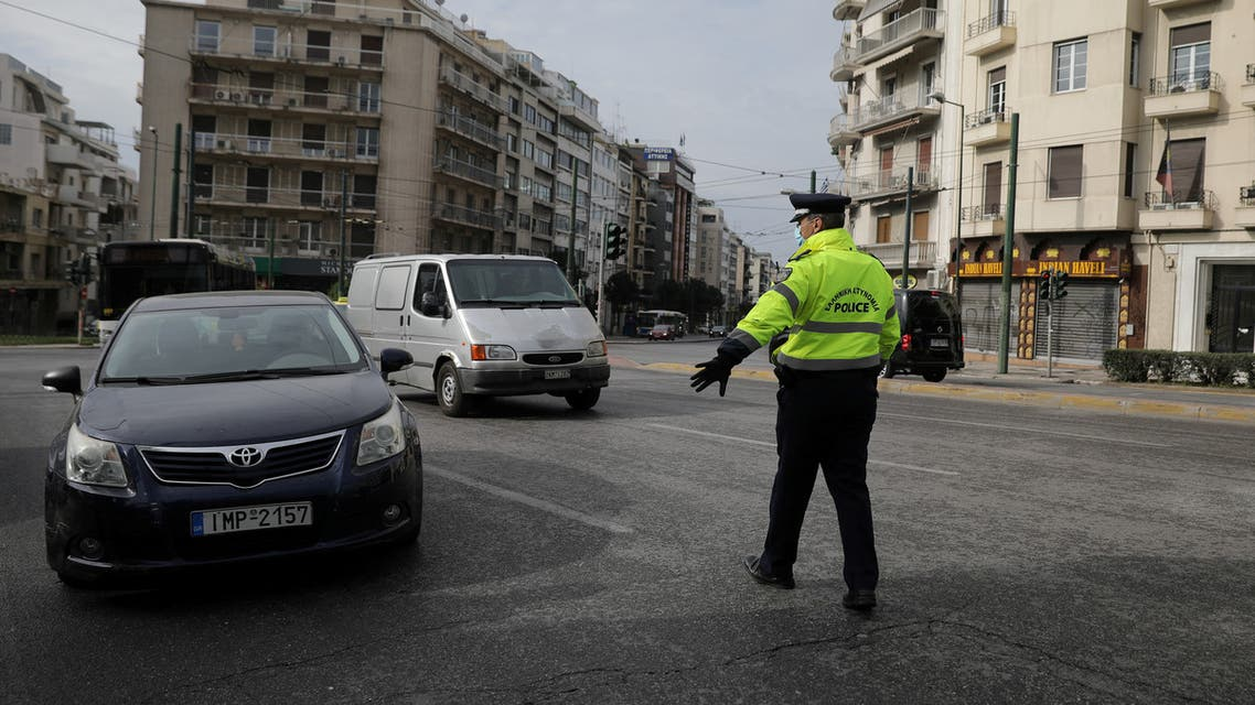 A police officer stops cars to perform checks on drivers' documents verifying purpose of movement, after the Greek government imposed a nationwide lockdown to contain the spread of the coronavirus disease (COVID-19), in Athens, Greece, March 23, 2020. REUTERS/Costas Baltas