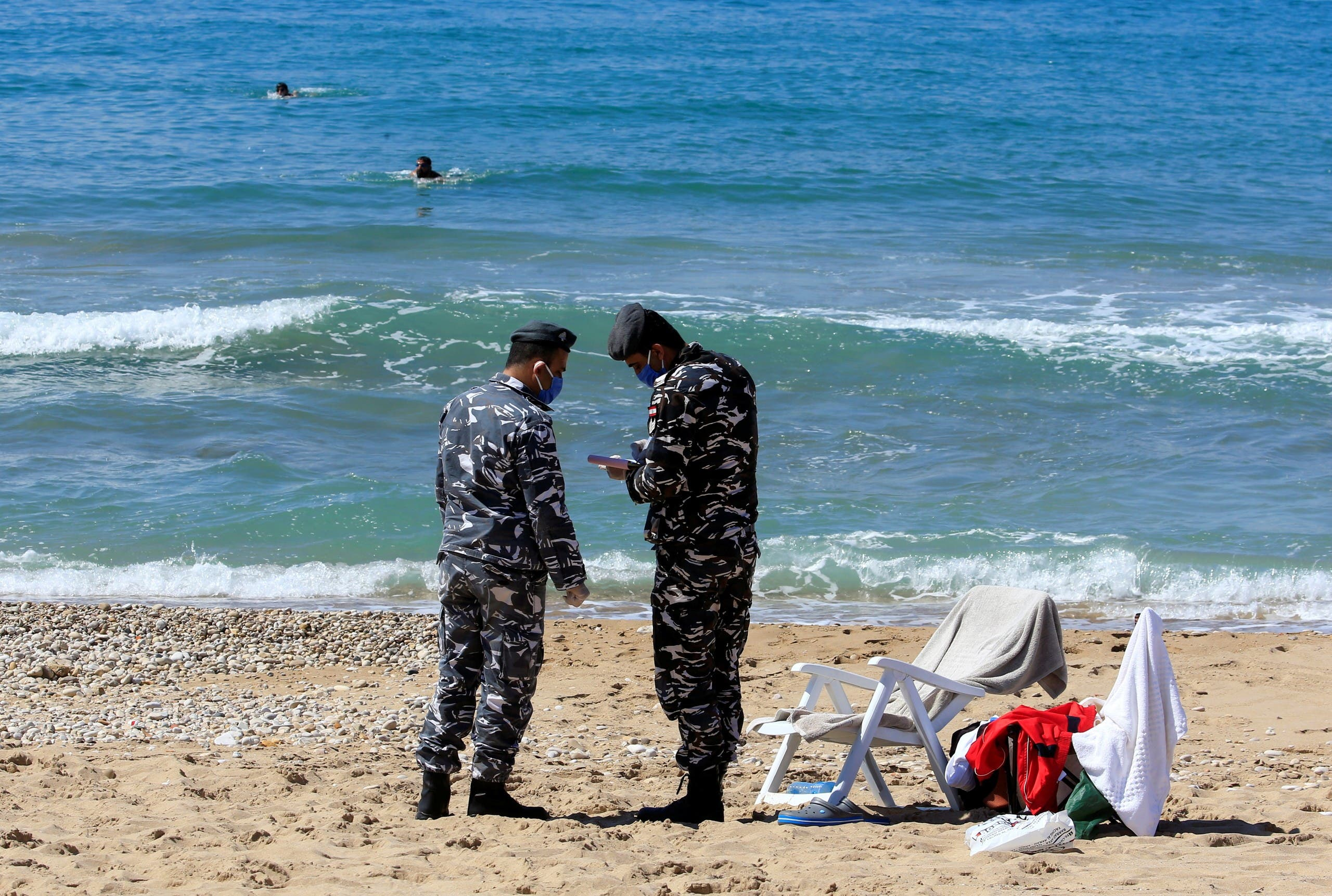 Lebanese officials issue fines at the beach in Sidon amid the nation-wide lockdown, March 22. (Reuters)