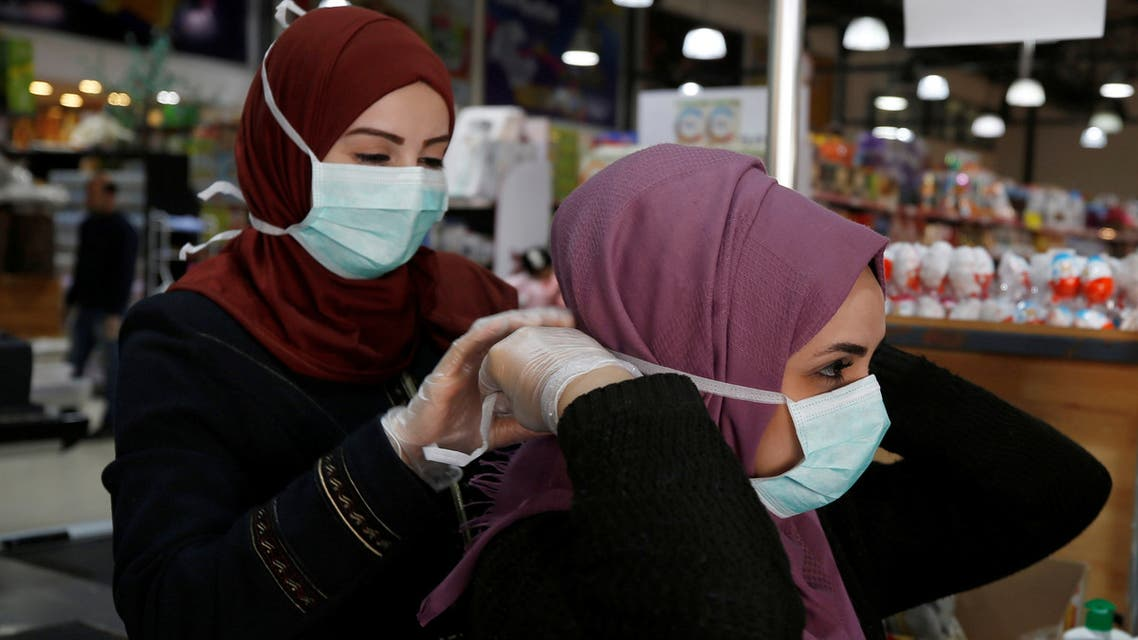A Palestinian cashier is helped by her colleague to wear a mask amid coronavirus precautions, in a supermarket in Gaza City March 8, 2020. Picture taken March 8, 2020. REUTERS/Mohammed Salem