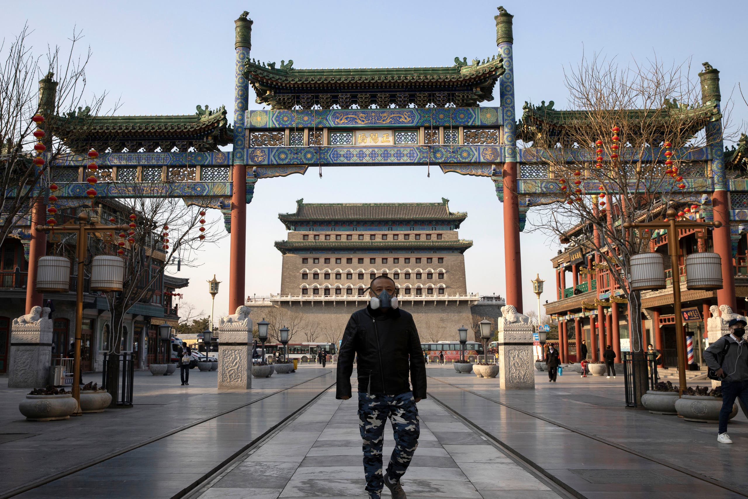 A man wearing a face mask walks through a quiet retail district in Beijing on on March 23, 2020. (AP)
