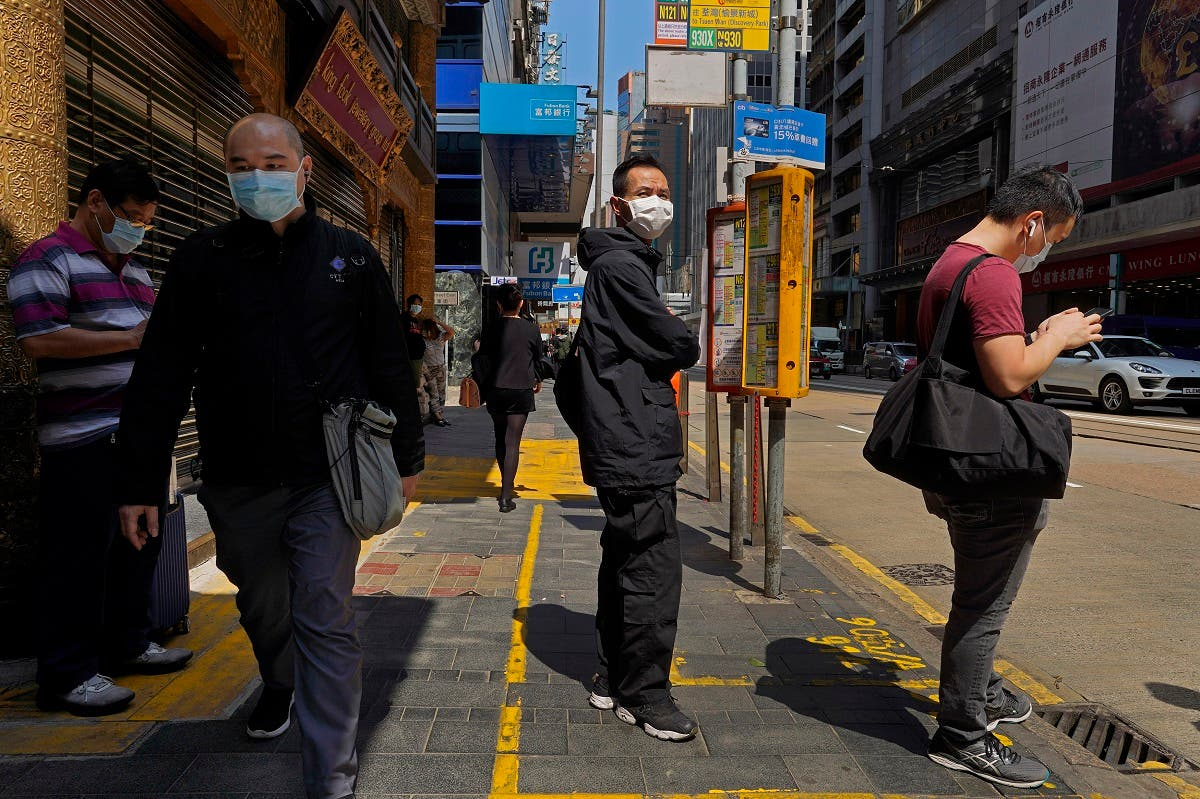 People wearing face masks walk at a down town street in Hong Kong Monday, March 23, 2020. (AP)