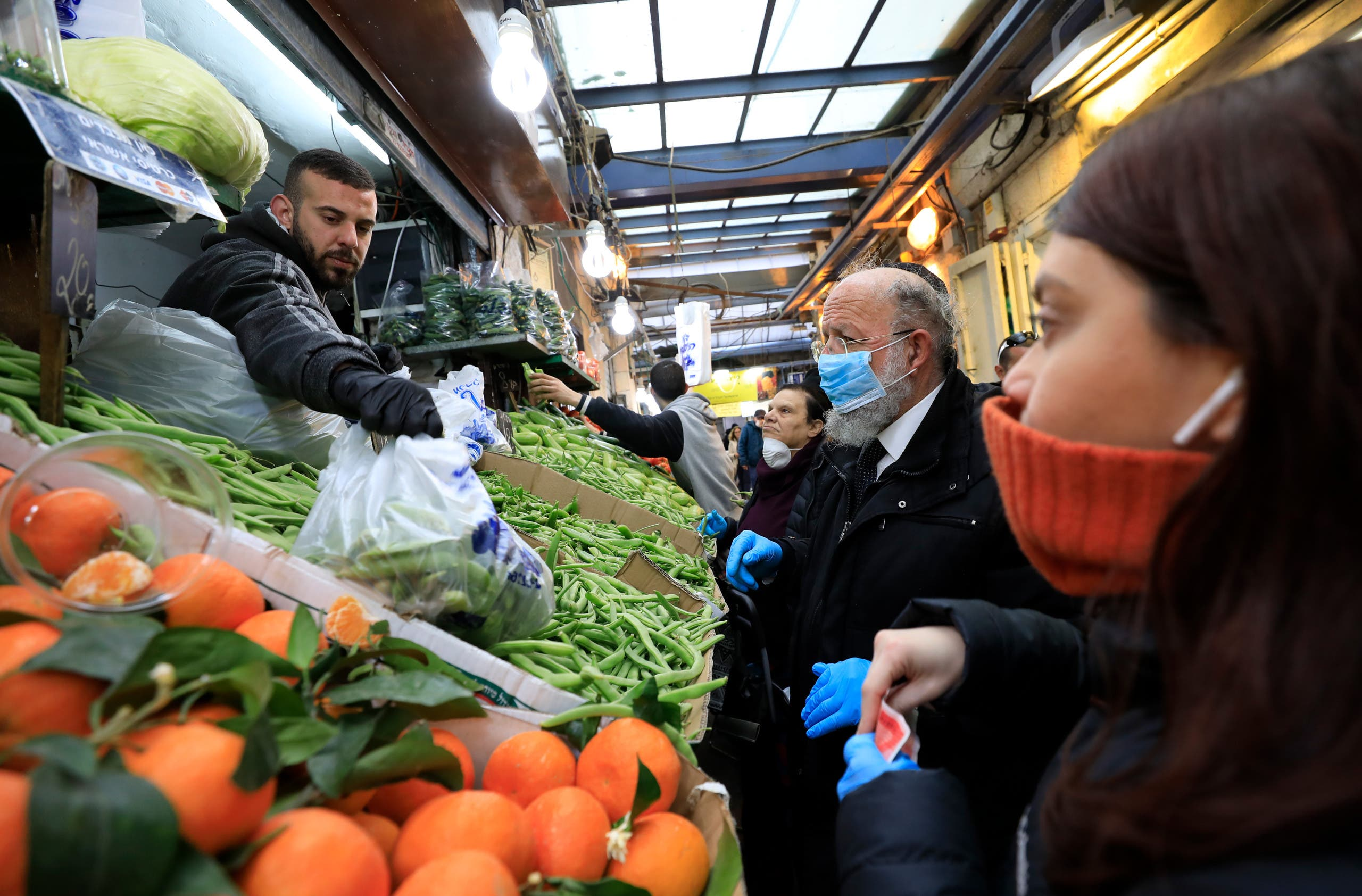 People wearing masks shop at Jerusalem's Mahane Yehuda market on March 19, 2020. (AP)