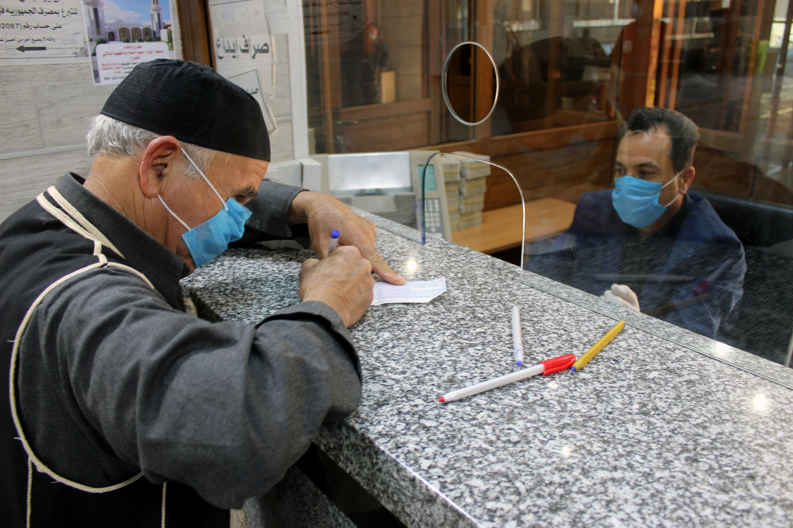 Men wear face masks at a bank in Libya, March 22. (Reuters)