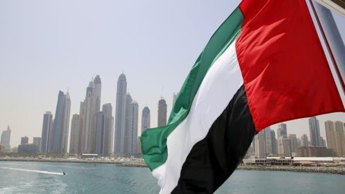 UAE flag flies over a boat at Dubai Marina