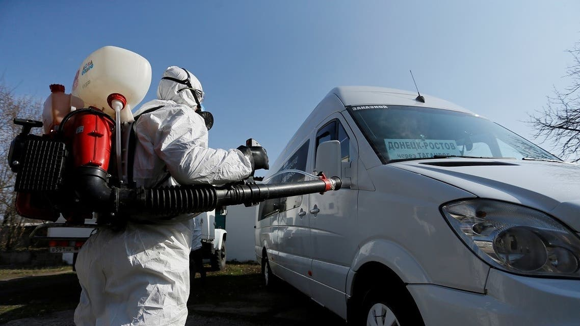 A worker wearing a protective suit sprays disinfectant on a bus as a preventive measure against the spread of coronavirus disease (COVID-19) in Donetsk. (Reuters)