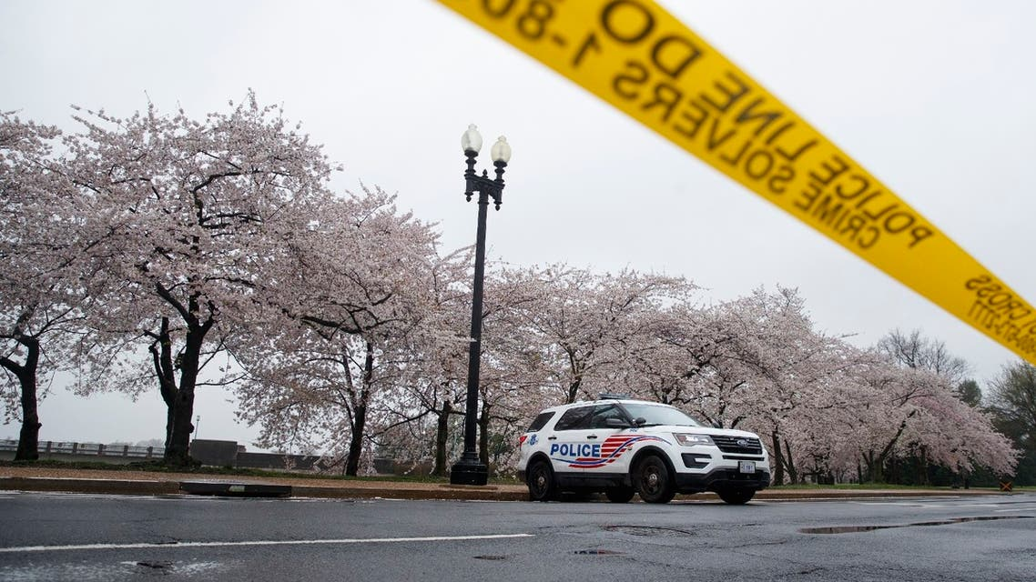 A Washington, D.C. Metropolitan Police vehicle is parked on the other side of a tape police line along the Tidal Basin as cherry blossoms cover the trees, in Washington, March 23, 2020.