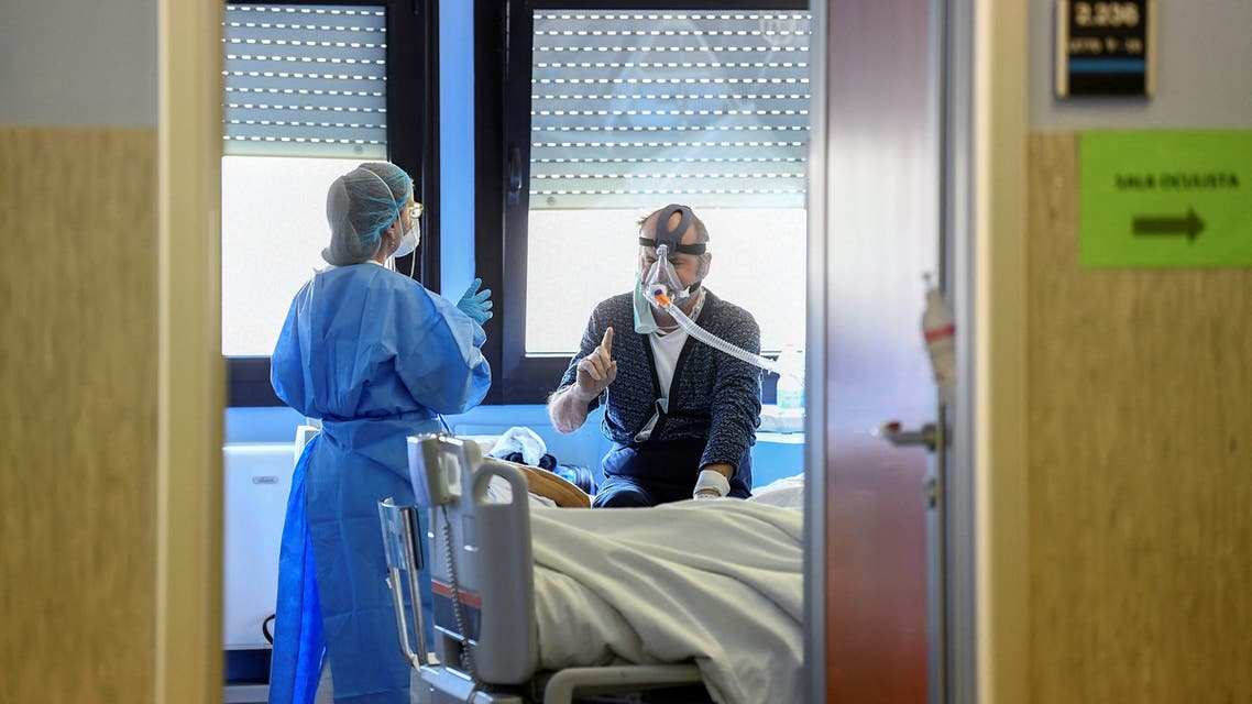 A medical worker wearing a protective mask and suit speaks with a patient suffering from coronavirus disease (COVID-19) in an intensive care unit at the Oglio Po hospital in Cremona, Italy March 19, 2020. REUTERS/Flavio Lo Scalzo