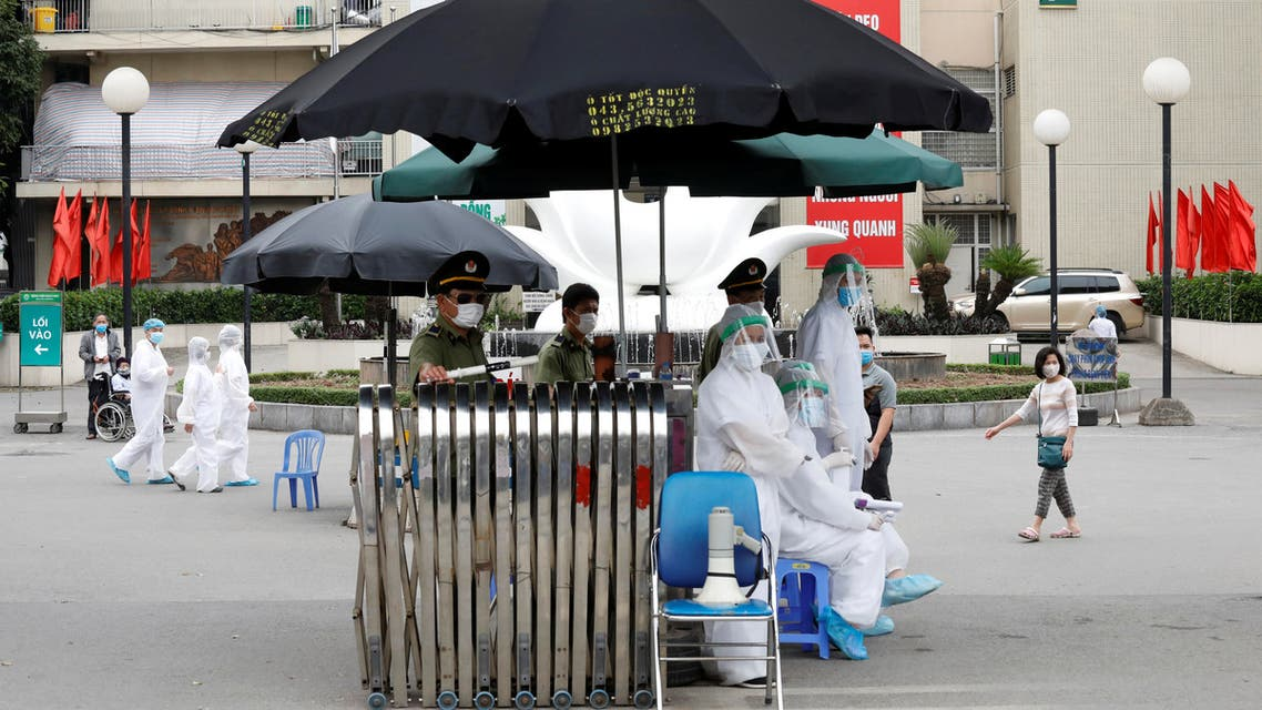 Health workers in hazmat suits are seen at the gate of Vietnam's largest hospital, Bach Mai, where coronavirus cases have been detected in Hanoi, Vietnam March 26, 2020. REUTERS/Kham