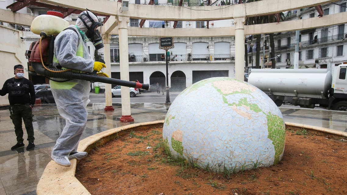 A worker wearing a protective suit disinfects a globe-shaped public garden, following the outbreak of coronavirus disease (COVID-19), in Algiers, Algeria March 23, 2020. REUTERS / Ramzi Boudina