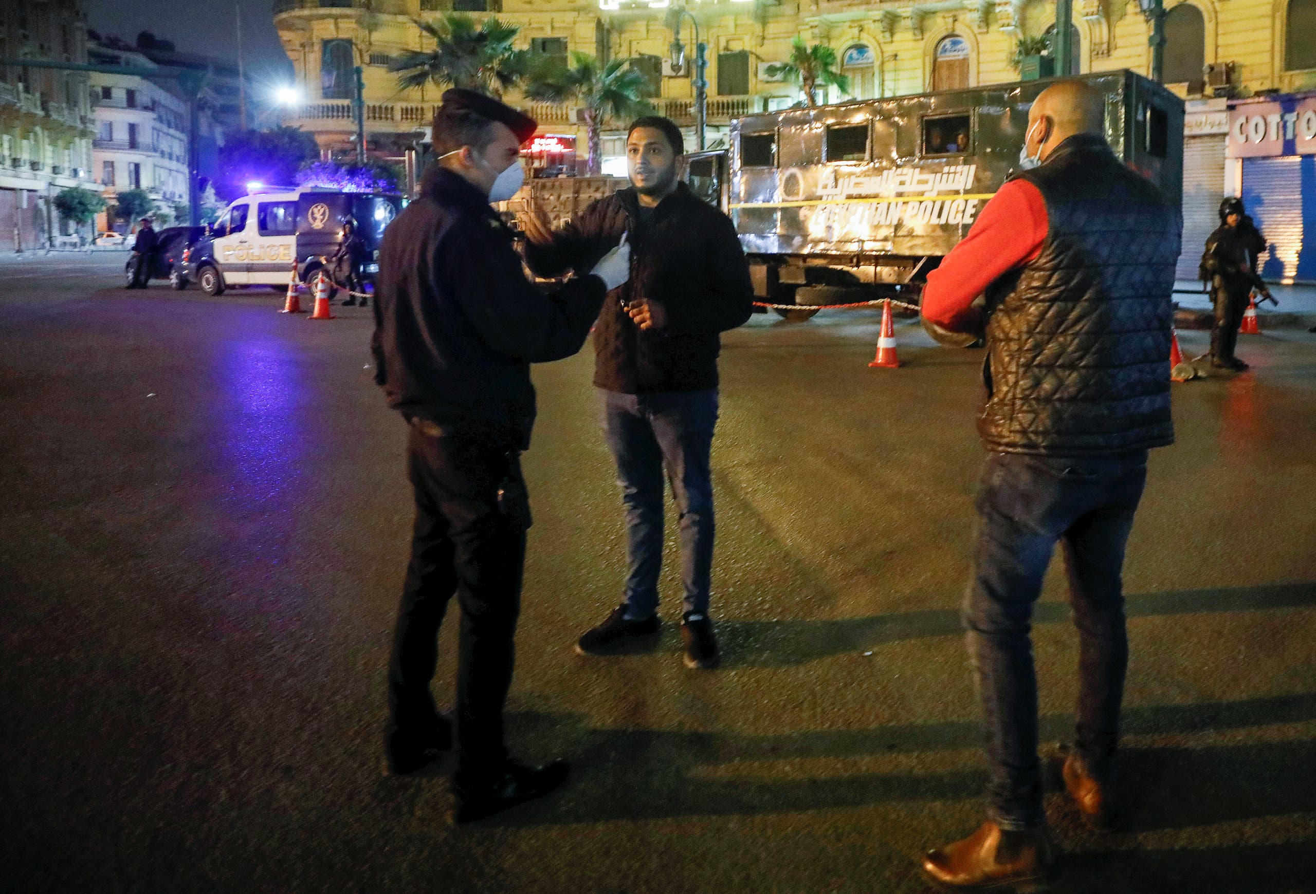 A police officer debriefs a man, near Tahrir square during the first day of a two-weeks night-time curfew in Cairo. (Reuters)