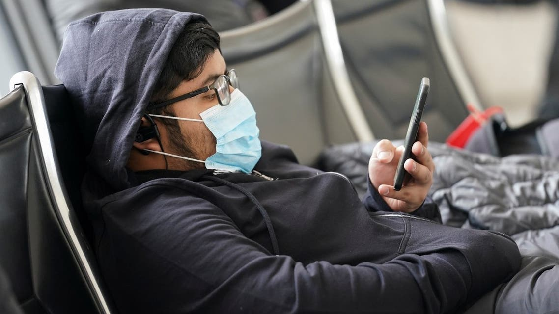 A man wearing a face mask looks at his phone at Dulles International Airport, a day after US President Donald Trump announced travel restrictions on flights from Europe to the United States for 30 days to try to contain the spread of the coronavirus, in Dulles, Virginia, US, March 12, 2020. (Reuters)