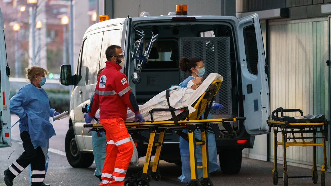 Paramedics wheel a patient into the Burgos general hospital in Burgos on March 25, 2020.  (AFP)