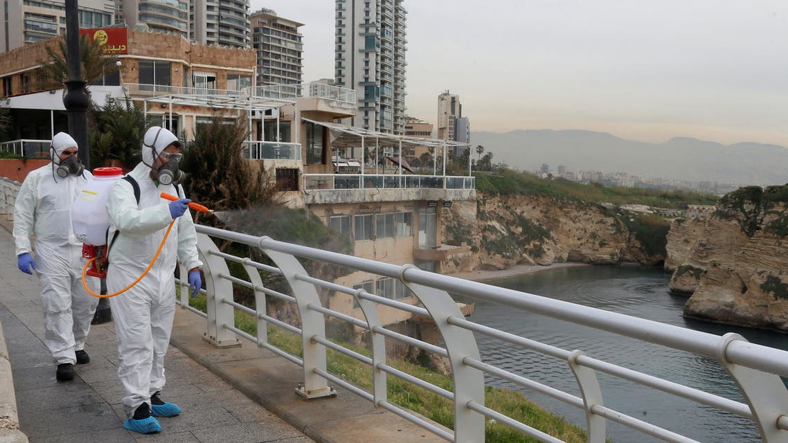 Employees from a disinfection company sanitize handrails, as a precaution against the spread of the coronavirus, at Beirut's seaside Corniche. (Reuters)