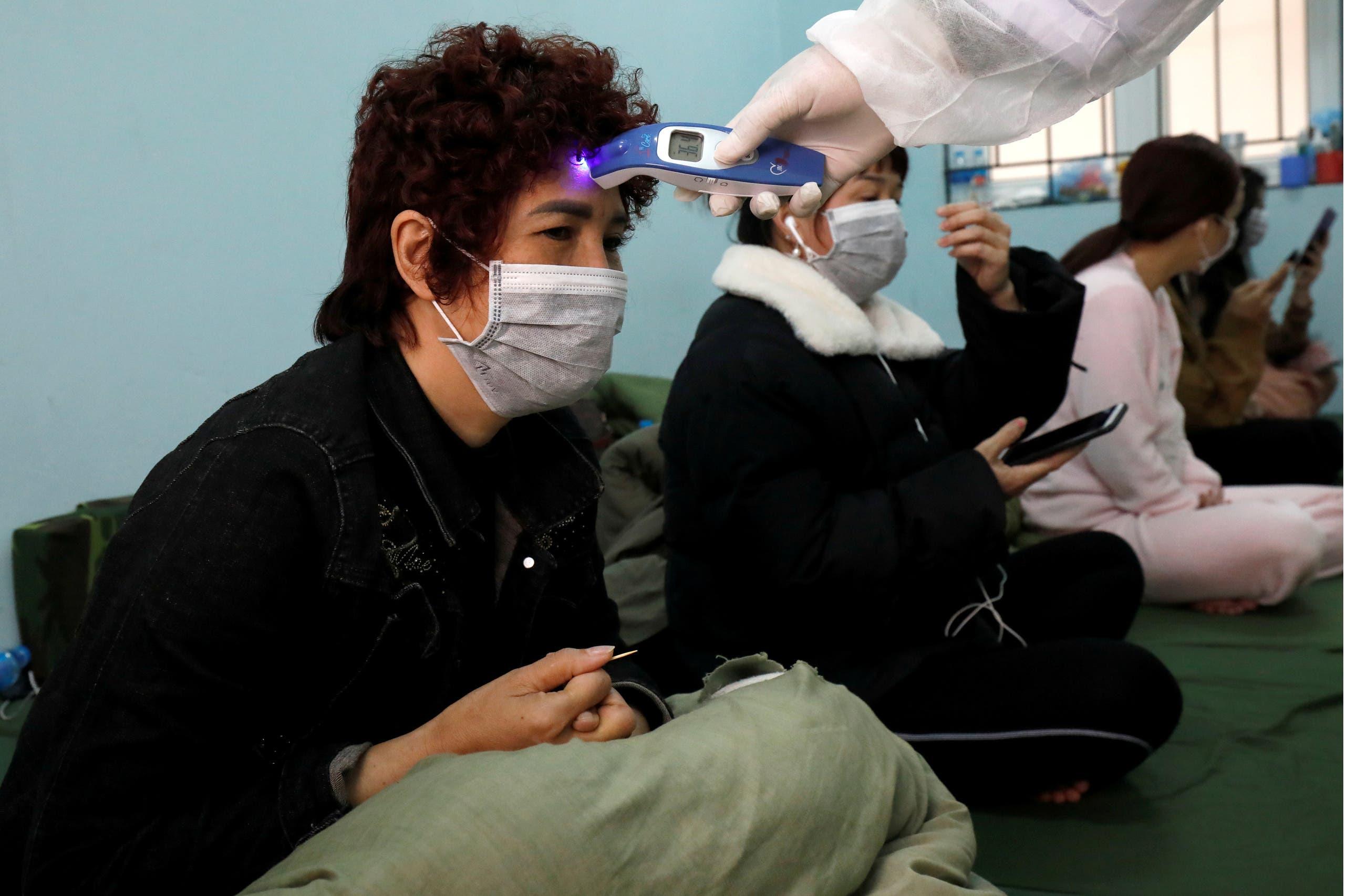 طبيب عسكري يفحص مسافرين عائدين من الصين