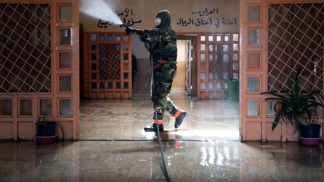 أحد العاملين بالدفاع المدني يقوم برش مطهرات في كربلاء بالعراق