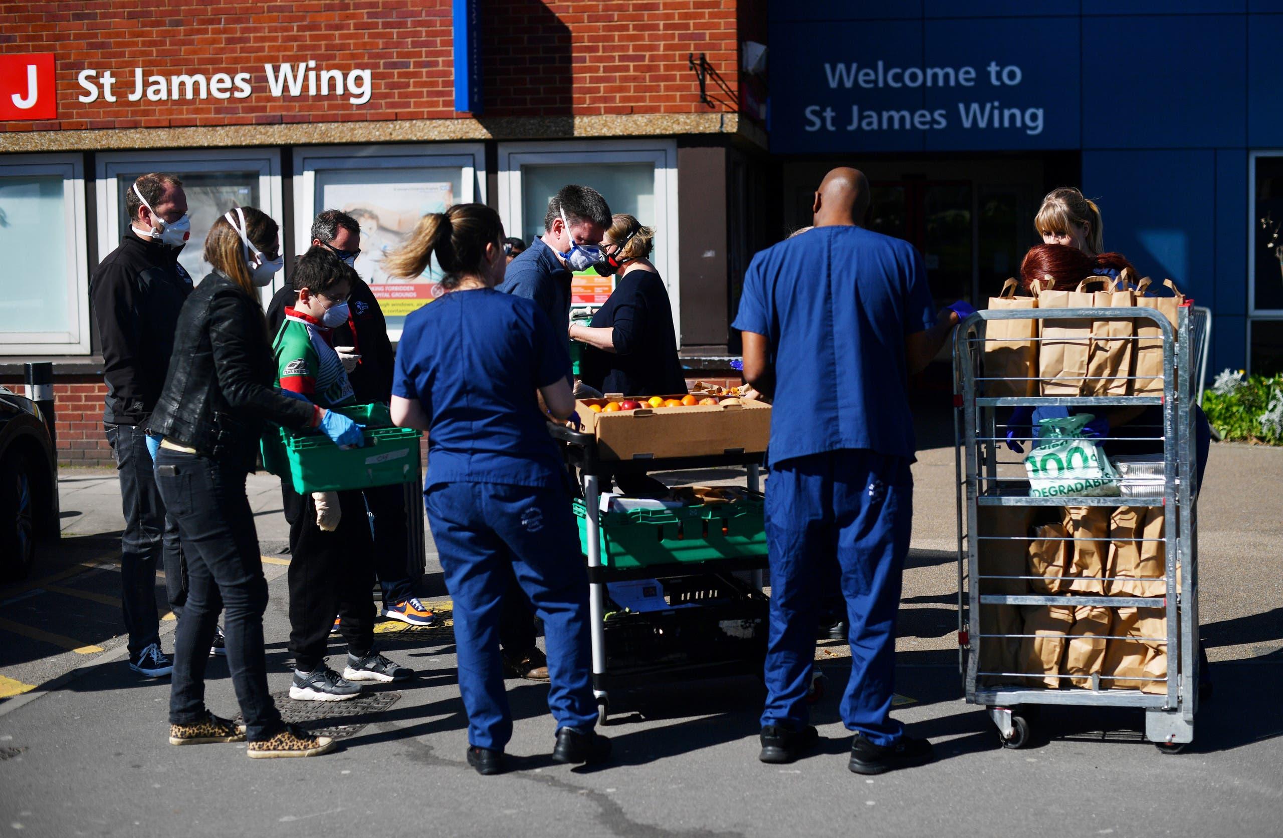 متطوعون يوصلون وجبات طعام إلى الممارسين الصحيين في أحد مستشفيات لندن