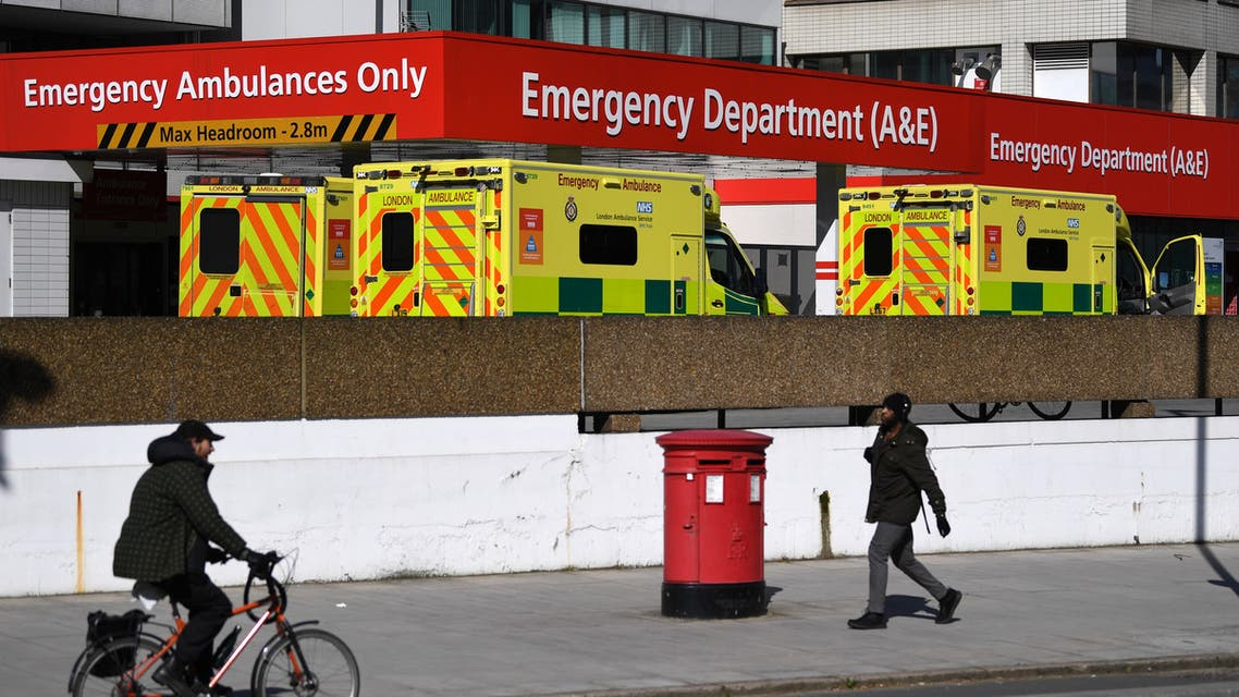 People make their way past ambulances waiting beside the Emergency Department of St Thomas' hospital in central London, March 23, 2020, as governments scramble to defend their own economies against the coronavirus COVID-19 pandemic in order to ward off a long-term global recession and future waves of infections