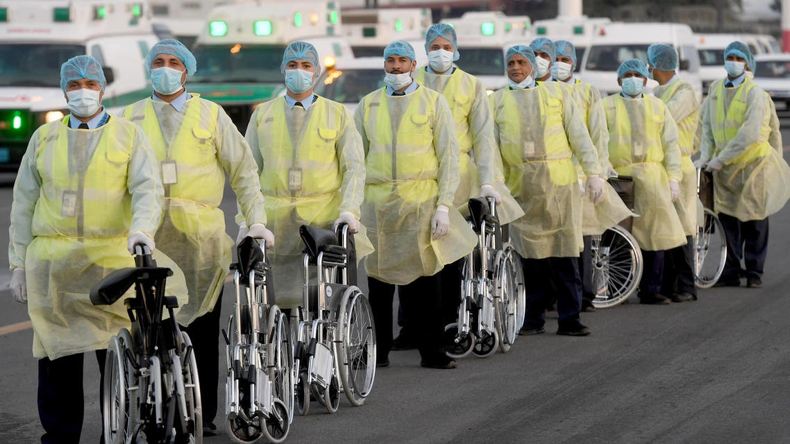 Health ministry workers, wearing protective outfits, wait on the tarmac of the Kuwait international Airport to receive Kuwaitis returning from Frankfurt on March 26, 2020, to be taken to a hospital for novel coronavirus checkups, in the capital Kuwait City.