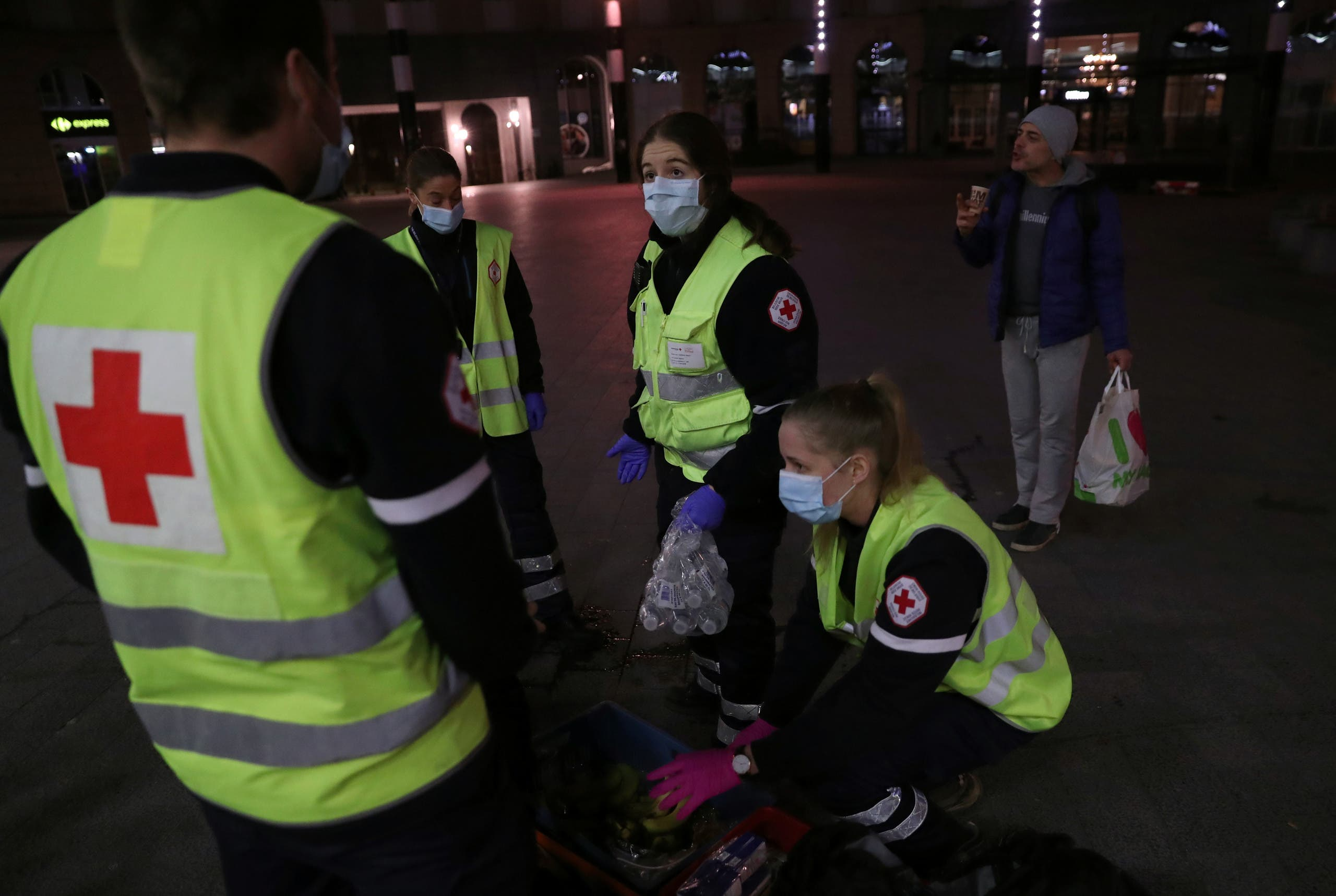 Members of the Belgian Red Cross carry food and drinks for homeless people near Brussels Central Station during the coronavirus lockdown imposed by the Belgian government in an attempt to slow down the coronavirus, in Brussels, Belgium March 25, 2020. (Reuters)