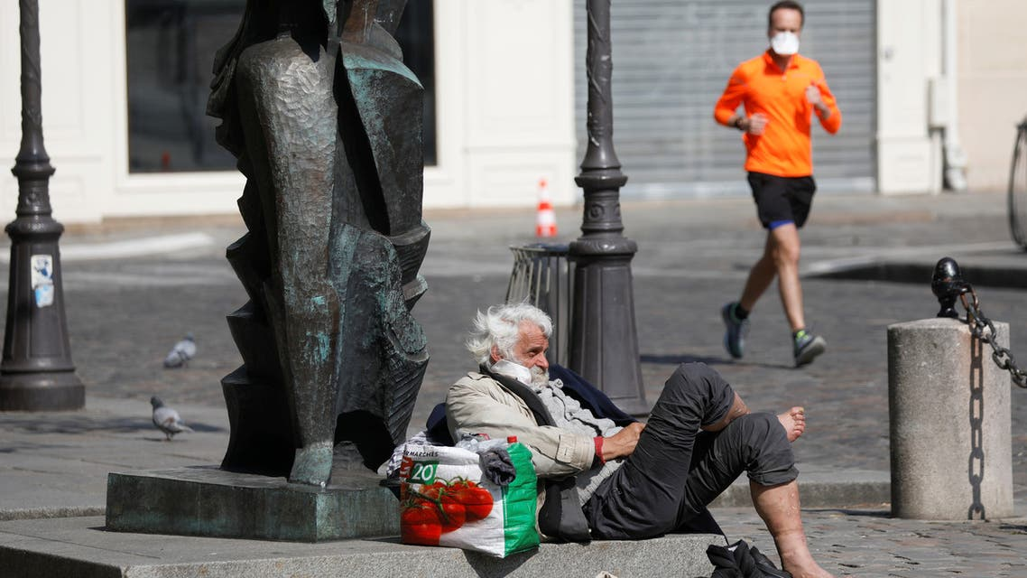 A lone jogger, wearing a protective face mask, passes by a homeless person in a street in Paris during the outbreak of Coronavirus disease (COVID-19) in France, March 27, 2020. REUTERS/Charles Platiau