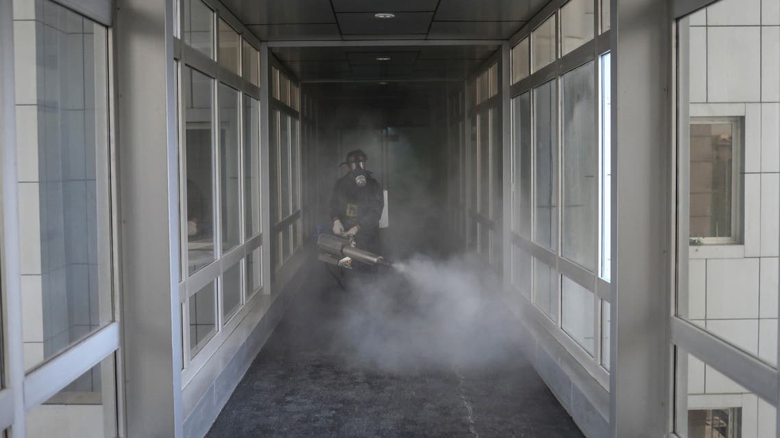A member of firefighters wears a protective face mask, amid fear of coronavirus disease (COVID-19), as he disinfects a municipality building, ahead of the Iranian New Year Nowruz, March 20, in Tehran. (Reuters)