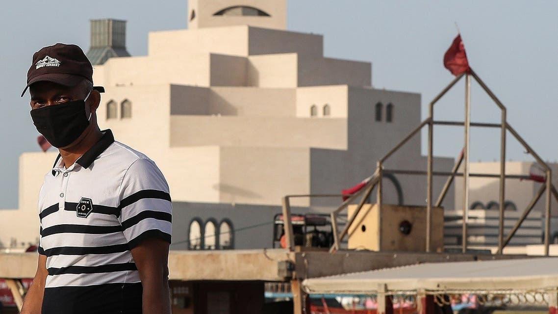 A man wearing a mask, precaution against COVID-19 coronavirus disease, walks along the Doha corniche near the Qatar Islamic Museum in the Qatari capital. (AFP)