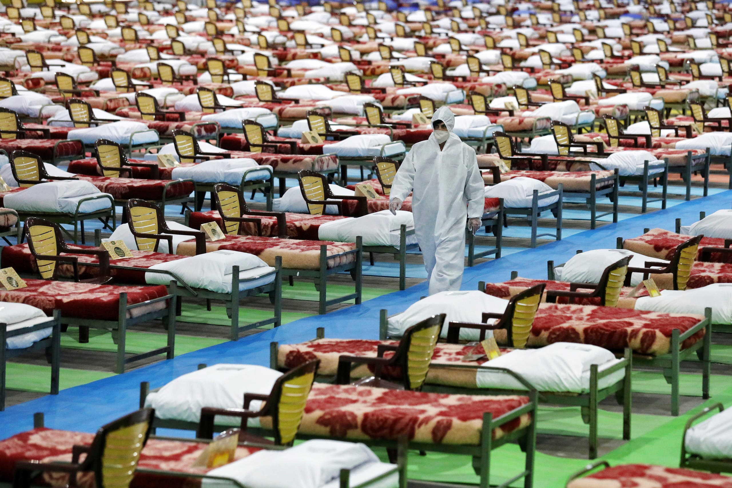 People in protective clothing walk past rows of beds at a temporary 2,000-bed hospital for COVID-19 patients set up by the Iranian army in northern Tehran, Iran, on Thursday, March 26, 2020. (AP)