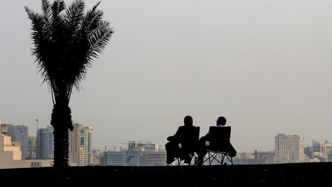 A couple sit on foldable seats along the promenade of the Doha corniche in the Qatari capital on March 16, 2020. (AFP)