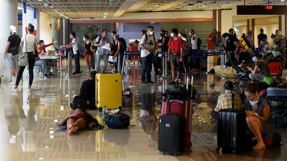 Stranded tourists (foreground) gather as French embassy staff (background L, at tables) process nationals ahead of their evacuation flight amid concerns from the COVID-19 coronavirus at the Ngurah Rai international airport near Denpasar. (AFP)