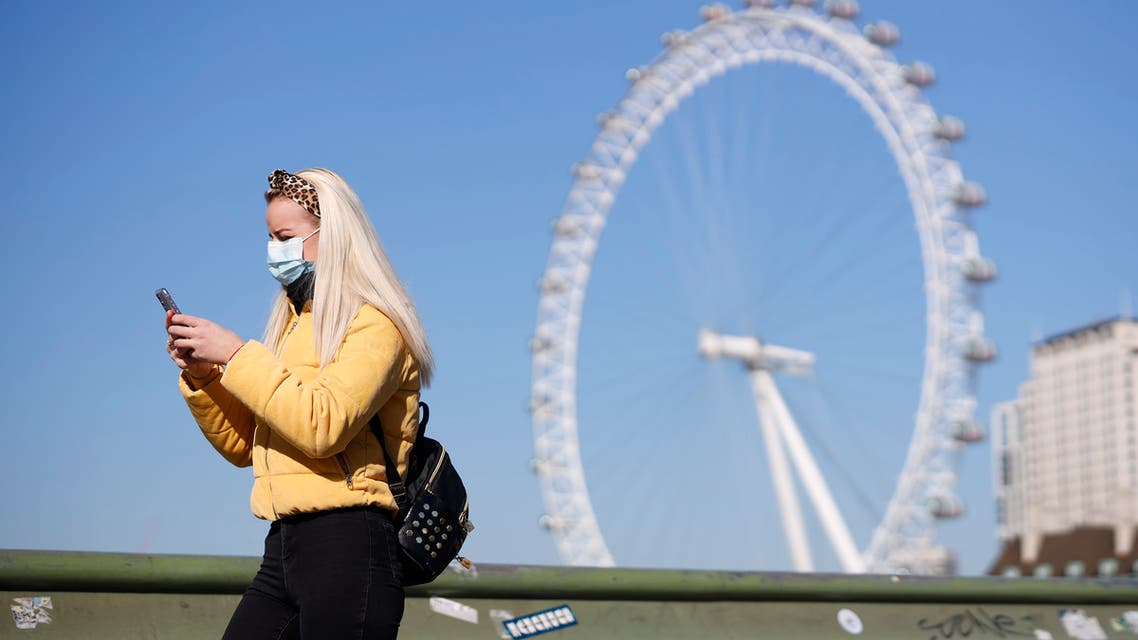 A pedestrian in a mask walks along Westminster Bridge with the London Eye in the backgroud, in a quiet central London on March 25, 2020, after Britain's government ordered a lockdown to slow the spread of the novel coronavirus. Britain was under lockdown, its population joining around 1.7 billion people around the globe ordered to stay indoors to curb the accelerating spread of the coronavirus.