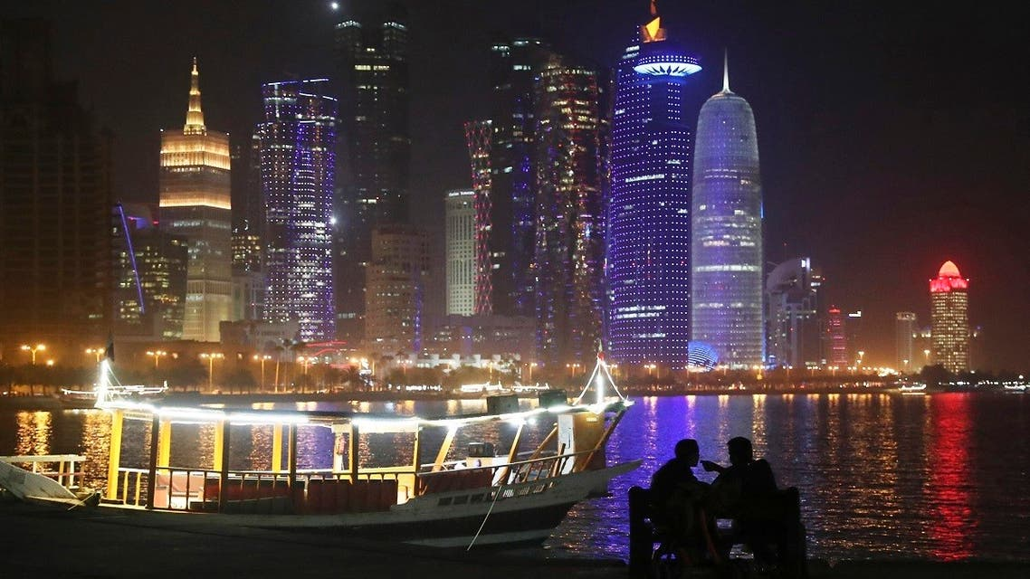 In this Tuesday, May 14, 2019 photo, two people take in the sea breeze at the Corniche waterfront promenade in Doha, Qatar, with a night view of skyline. (AP Photo/Kamran Jebreili)