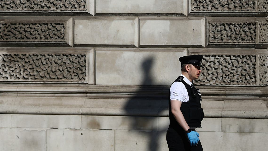 A police officer wearing gloves walks in Westminster, as the spread of coronavirus disease (COVID-19) continues. London, Britain, March 25, 2020. REUTERS/Hannah Mckay