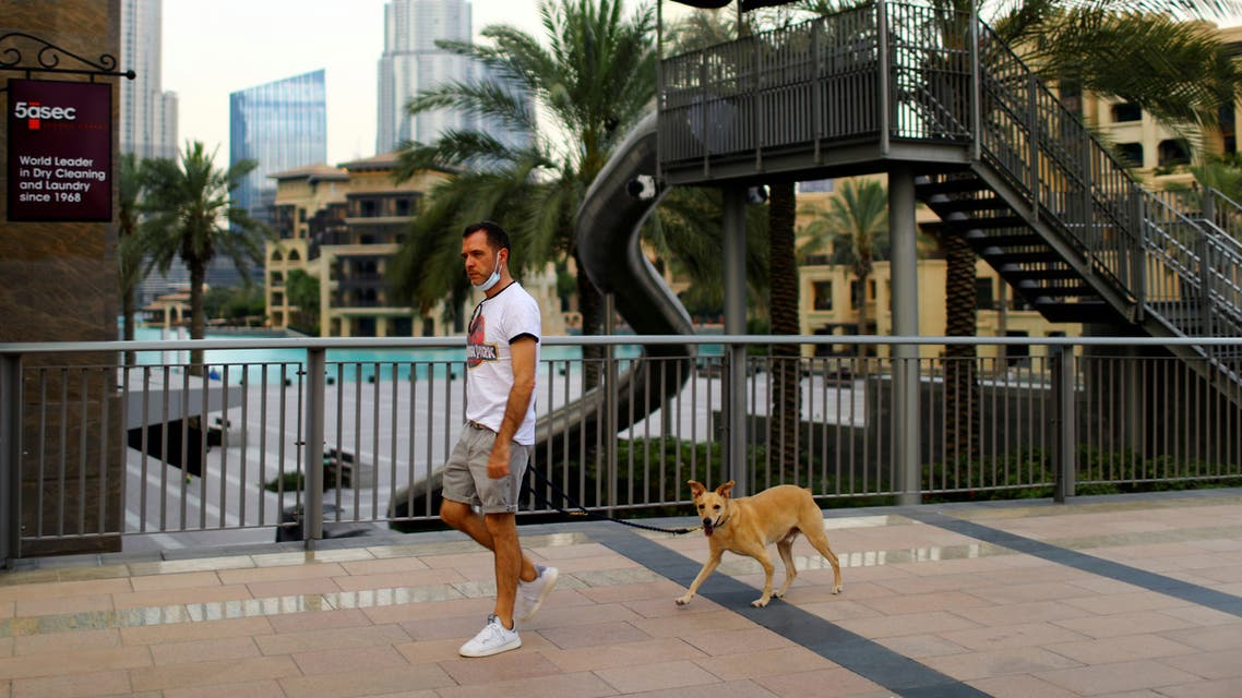 A man with a protective face mask, walks his dog, following the outbreak of coronavirus disease (COVID-19), in downtown Dubai. (Reuters)